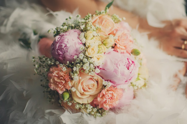 Closeup de buquê de casamento no vestido de noiva
