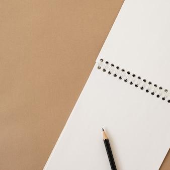Closeup de caderno espiral e lápis em pastel bege neutro. molde do espaço da cópia da folha do papel em branco. camada plana, vista superior.
