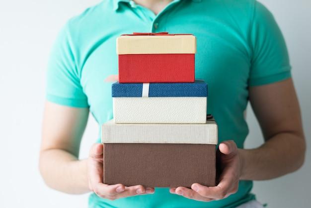 Closeup de cara segurando caixas de presente empilhadas