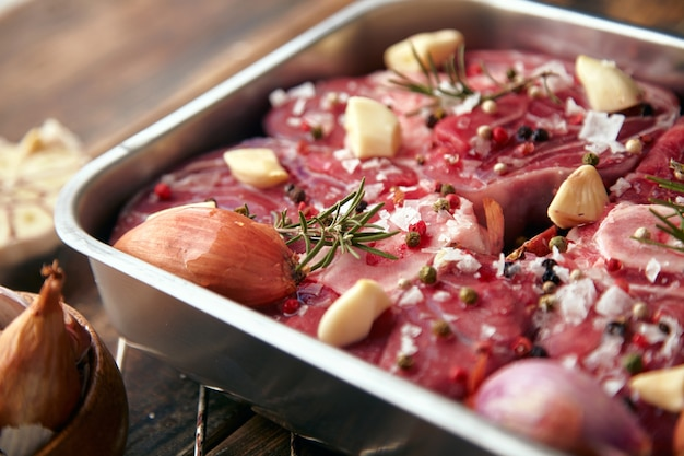 Closeup de carne em temperos de panela de aço ao redor: alho, alecrim, cebola