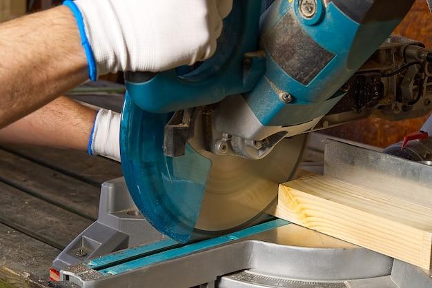 Closeup de carpinteiro profissional trabalhando com serra circular elétrica na oficina de carpintaria