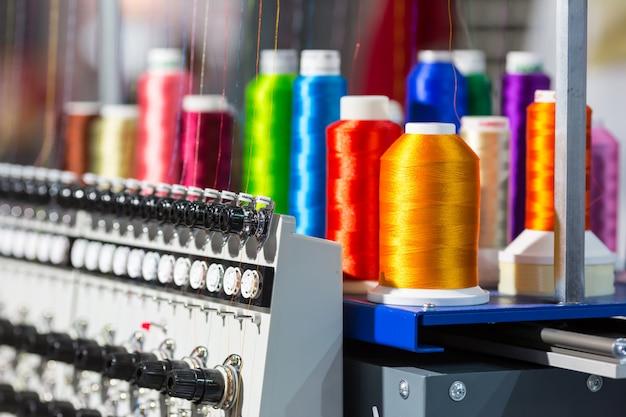 Closeup de carretéis de fios de cores, máquina de fiar