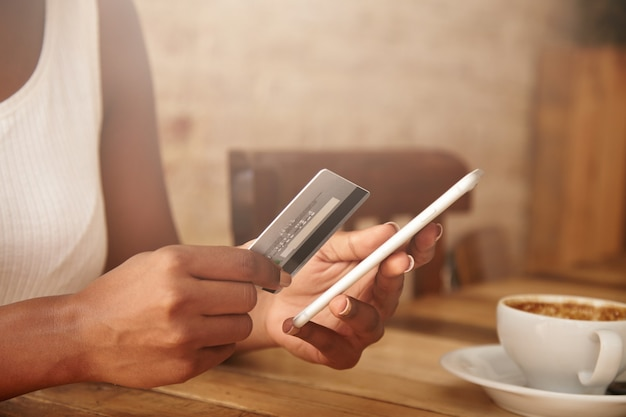 Closeup de cartão de crédito e smartphone nas mãos de uma mulher