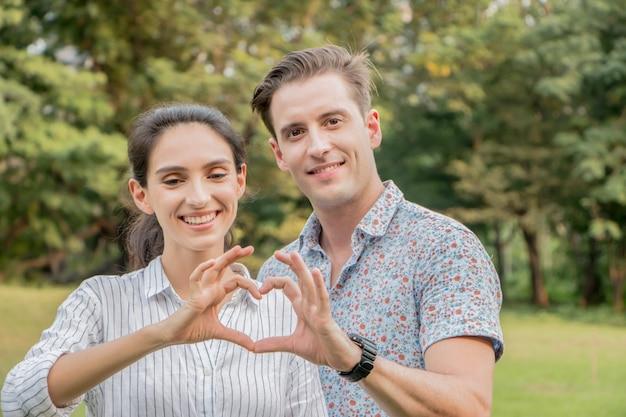 Closeup de casal fazendo formato de coração com as mãos