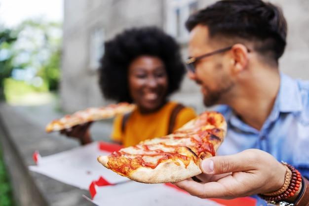 Closeup de casal jovem hippie multicultural sentado ao ar livre e comendo pizza. foco seletivo na mão humana.