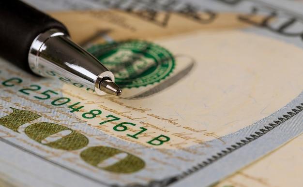 Closeup de cem dólares e caneta