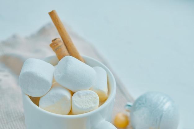 Closeup de chocolate quente com marshamllows e canela, decorações de natal em cima da mesa