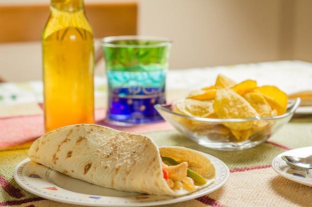 Closeup de comida tradicional mexicana em uma mesa, com um prato de fajita de frango, tigela de nachos e uma cerveja fresca