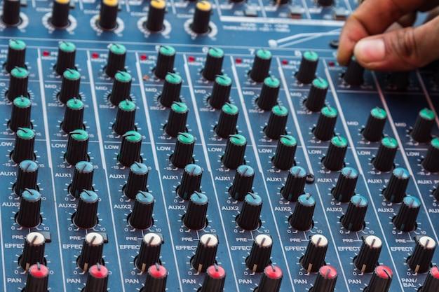 Closeup de console de mixagem de áudio com a mão