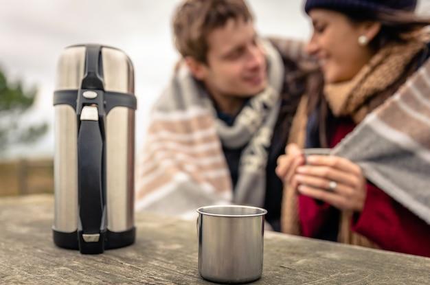 Closeup de copo metálico e garrafa térmica com bebida quente em uma mesa de madeira com o jovem casal sob o cobertor desfocado no fundo