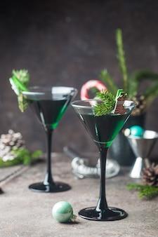 Closeup de coquetéis verdes em taças de martini com folhas de hortelã sobre cinza