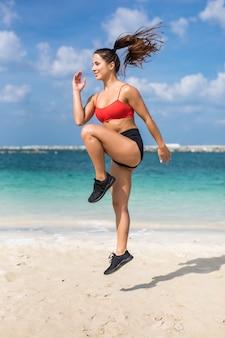 Closeup de corpo corredor fitness fazendo rotina de aquecimento na praia antes de executar