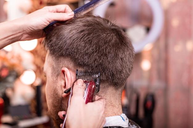 Closeup de corte de cabelo. mãos segurando uma máquina de cortar cabelo.