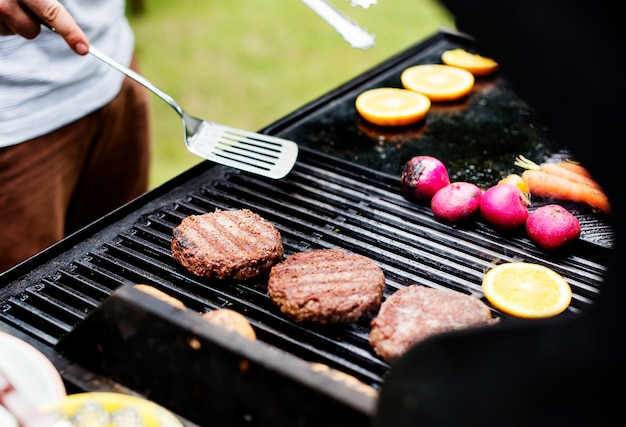 Closeup de cozinhar rissóis de hambúrguer na grelha de carvão
