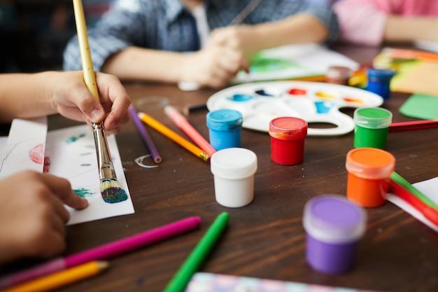 Closeup de crianças pintando na aula de arte