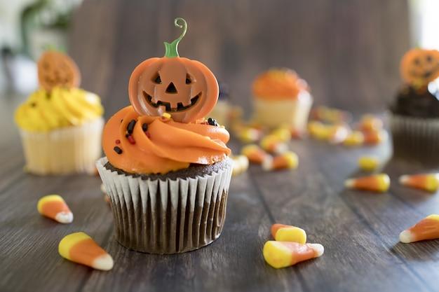 Closeup de cupcakes de halloween com coberturas coloridas e assustadoras na mesa