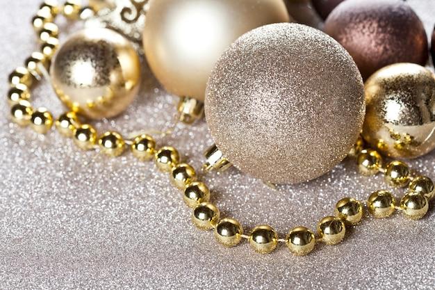 Closeup de decorações de ouro e marrom de natal em fundo de brilho.