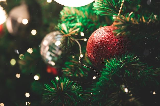 Closeup de decorar enfeites na árvore de natal com bokeh desfocado luz celebração e férias