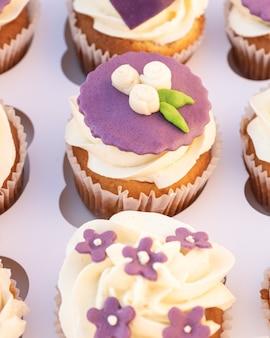 Closeup de deliciosos cupcakes caseiros com cobertura de açúcar em caixa de papel.