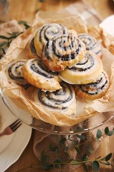 Closeup de deliciosos pastéis de caracol poppy com cobertura de açúcar em uma mesa de madeira