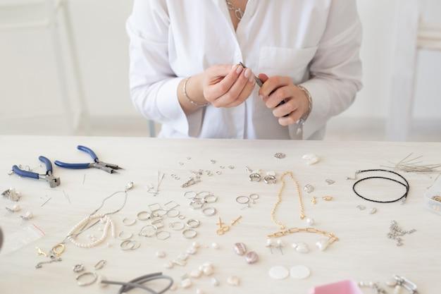 Closeup de designer de joias profissional fazendo joias feitas à mão em estúdio moda closeup