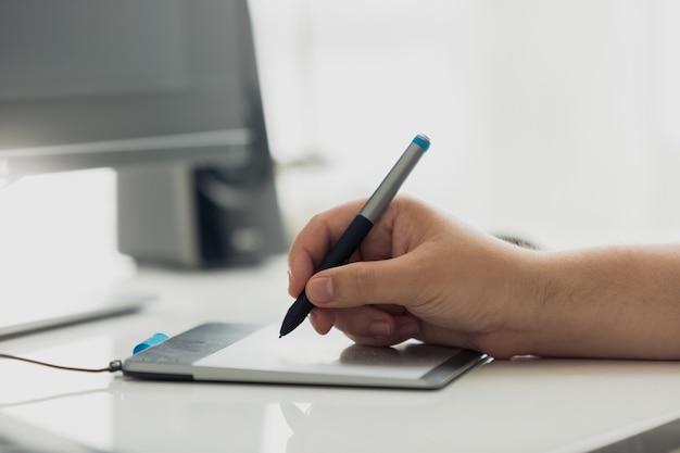 Closeup de designer profissional usando tablet gráfico no trabalho