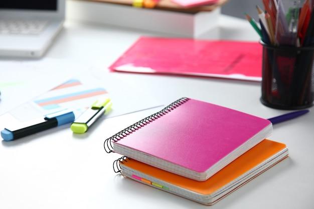 Closeup de desktop branco com blocos de notas, caneta e outros itens.