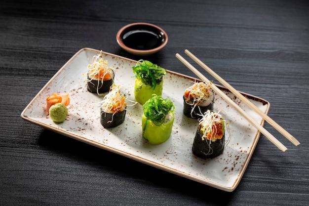 Closeup de diversos rolos de sushi na superfície escura, comida típica japonesa.