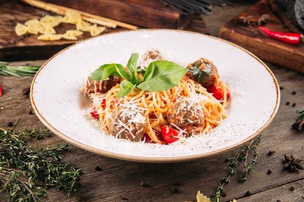 Closeup de espaguete italiano com almôndegas na mesa de madeira