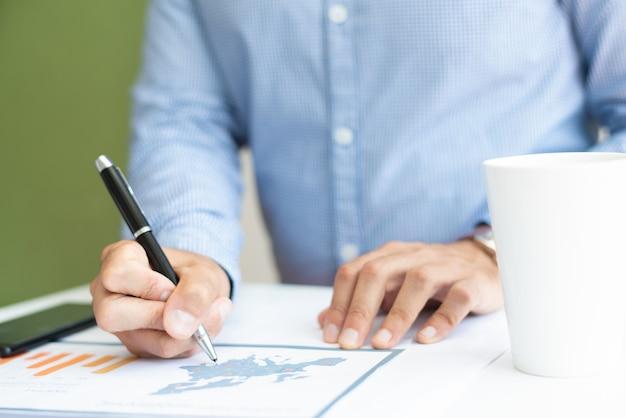 Closeup de especialista em marketing masculino, analisando o gráfico de barras