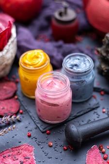 Closeup de especiarias coloridas para comida vegana em potes pequenos sobre a mesa com beterrabas desidratadas
