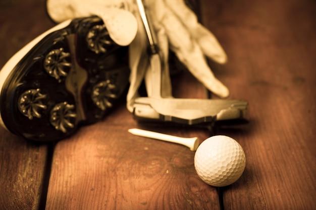 Closeup de espigões de tênis de golfe com luva, bola, tee e taco