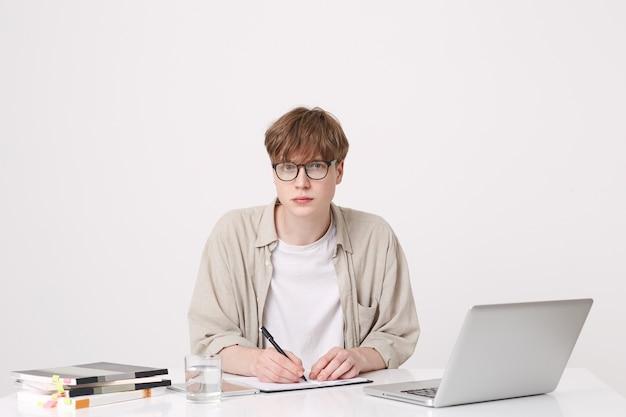 Closeup de estudante jovem bonito sério usa camisa bege e óculos, sentado com o computador laptop e notebooks na mesa e escrevendo isolado na parede branca