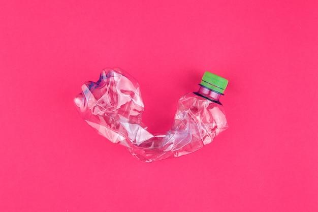 Closeup de garrafa pet esmagada em fundo rosa vívido
