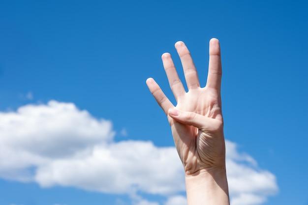 Closeup de gesto da mão de uma mulher mostrando quatro dedos, isolado em um fundo de céu azul com nuvens, símbolo número quatro da linguagem de sinais.