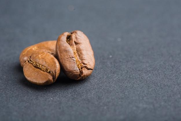 Closeup de grãos de café sobre fundo preto com copyspace