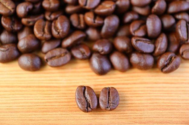 Closeup de grãos de café torrados de arábica vs robusta com a pilha de grãos de café borrados