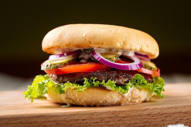 Closeup de hambúrguer clássico com hambúrguer de carne na placa de madeira