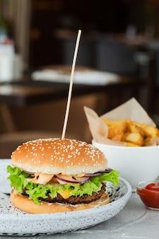 Closeup de hambúrguer com salada e molho na mesa de concreto, plano de fundo do restaurante. grande hambúrguer com batatas fritas e ketchup.