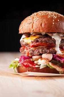 Closeup de hambúrguer em fundo preto em restaurante