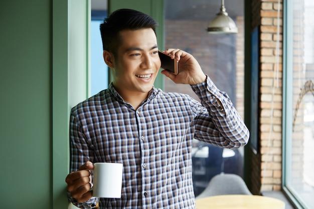 Closeup de homem asiático, segurando uma caneca de café, olhando pela janela enquanto fala ao telefone