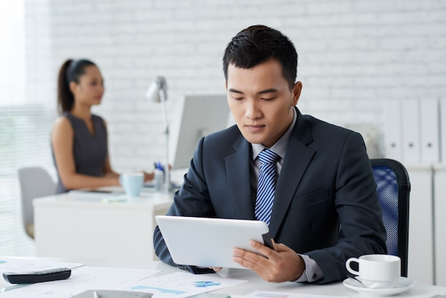 Closeup de homem em traje de gala sentado na mesa do escritório e trabalhando no tablet pc