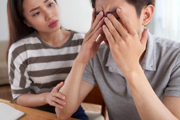 Closeup de homem enfrentando desafios financeiros consolados por sua esposa