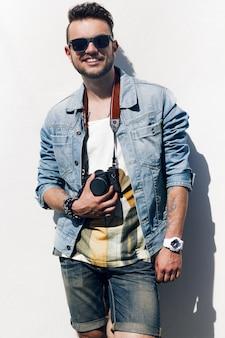 Closeup de homem jovem hippie com câmera sorrindo