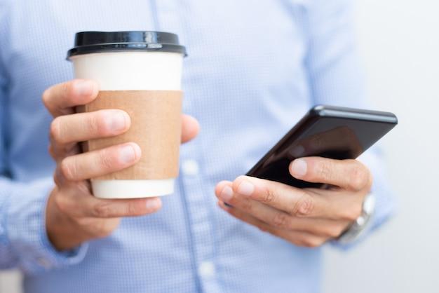 Closeup, de, homem negócio, segurando, smartphone, e, bebida