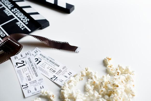 Closeup de ingressos de cinema com pipoca e bobinas de decoração na mesa branca