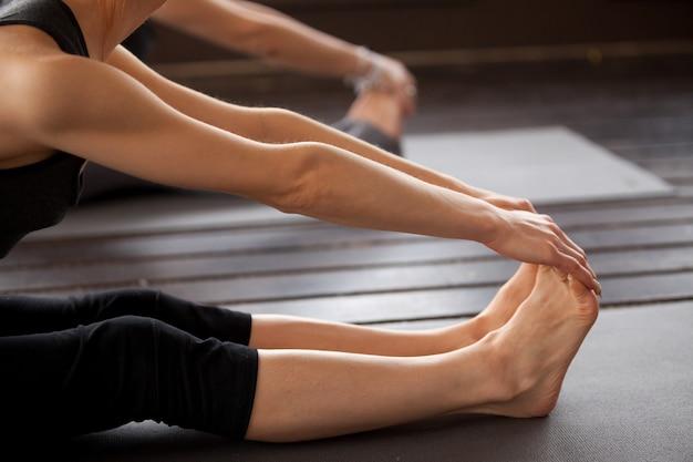 Closeup, de, iogue, mulher, em, paschimottanasana, pose