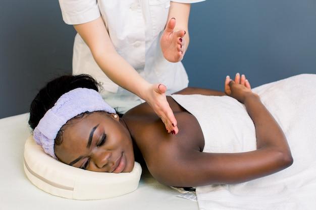 Closeup de jovem africana relaxada recebendo massagem nos ombros de massagista no spa