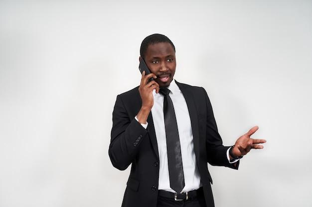Closeup de jovem africano irritado gritando enquanto falava no smartphone