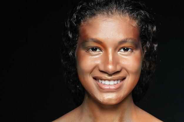 Closeup de jovem americana alegre com maquiagem criativa sobre preto
